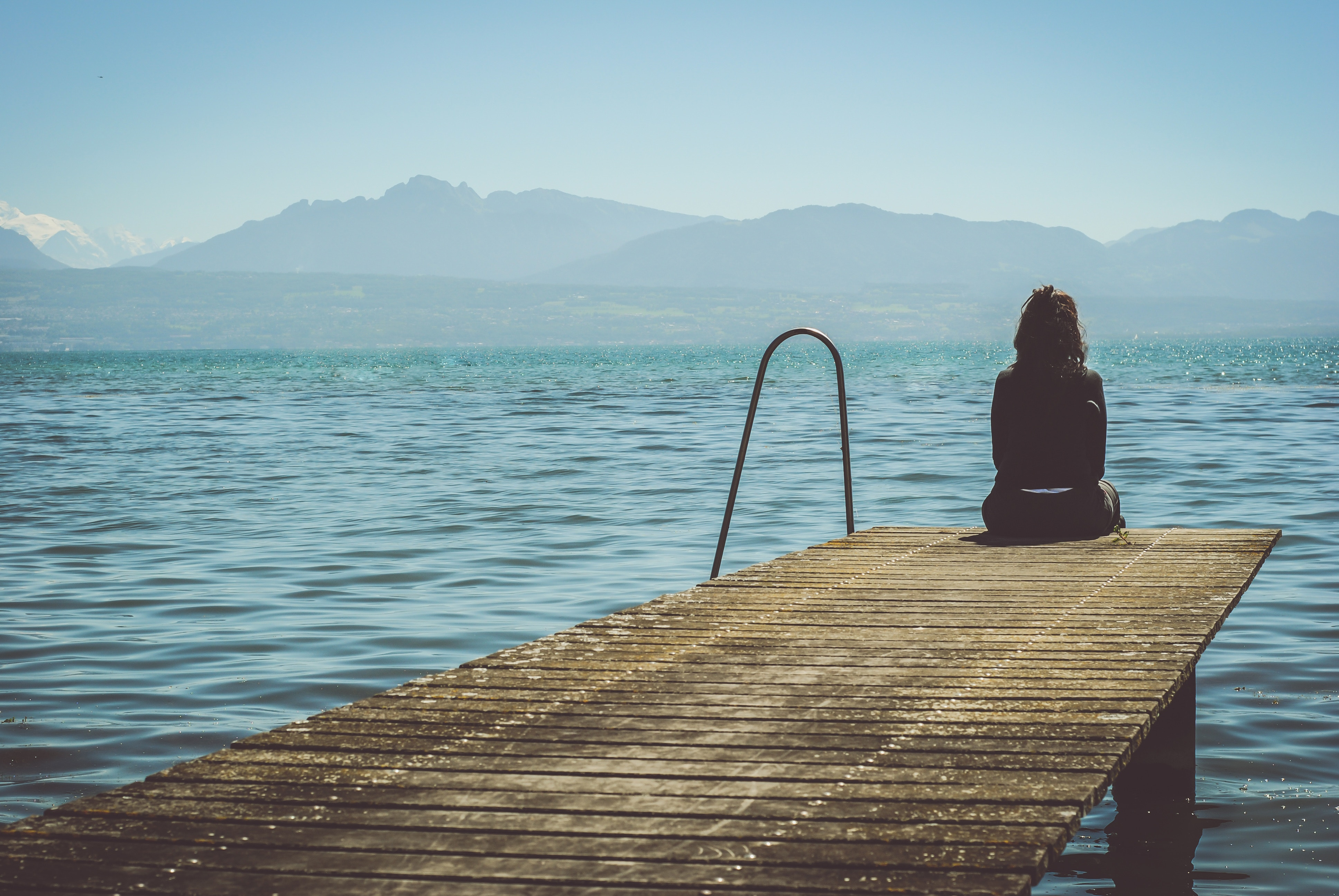 A girl in Morges sits at the end of a dock and stares at the mountains